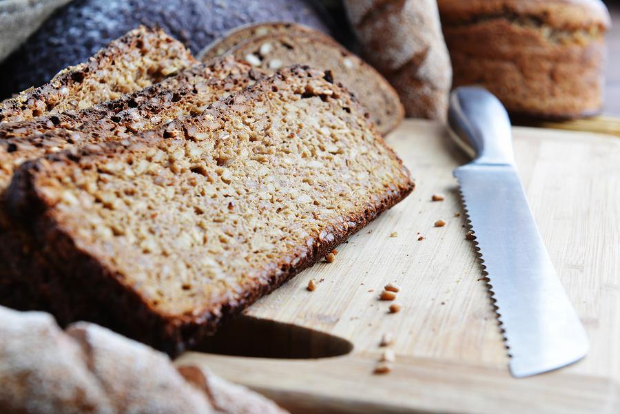 Ezekiel Bread sliced on a wooden cutting board